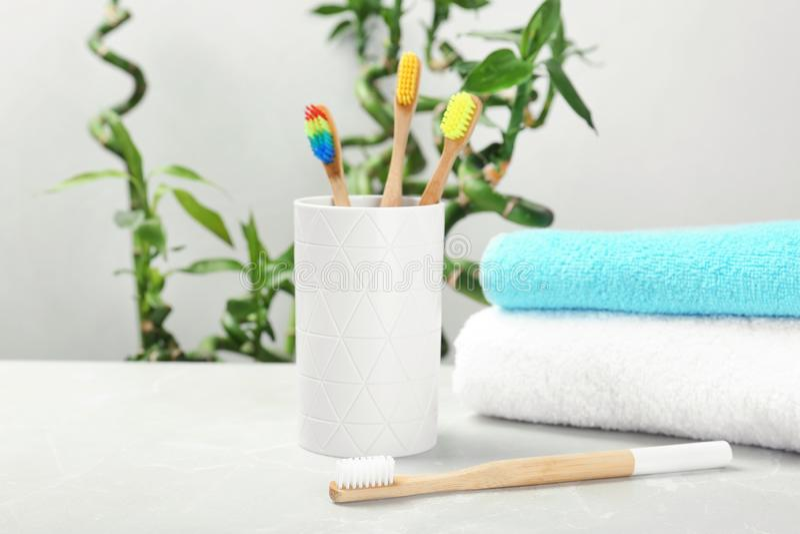 Escovas de dentes e suporte de bambu na tabela imagens de stock