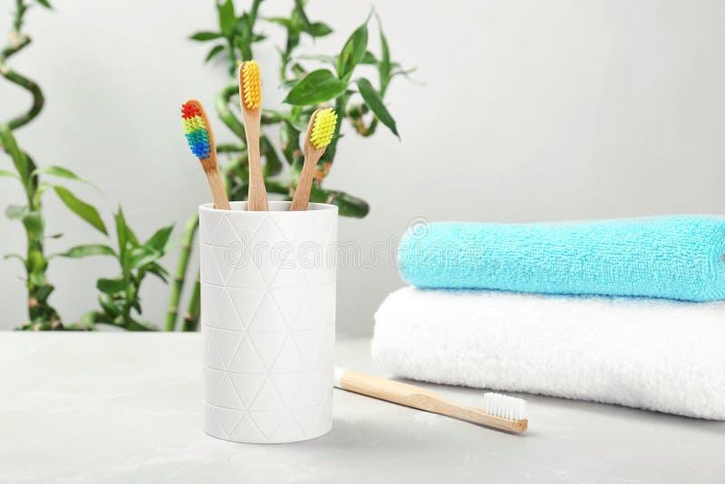 Escovas de dentes e suporte de bambu na tabela dentro imagem de stock