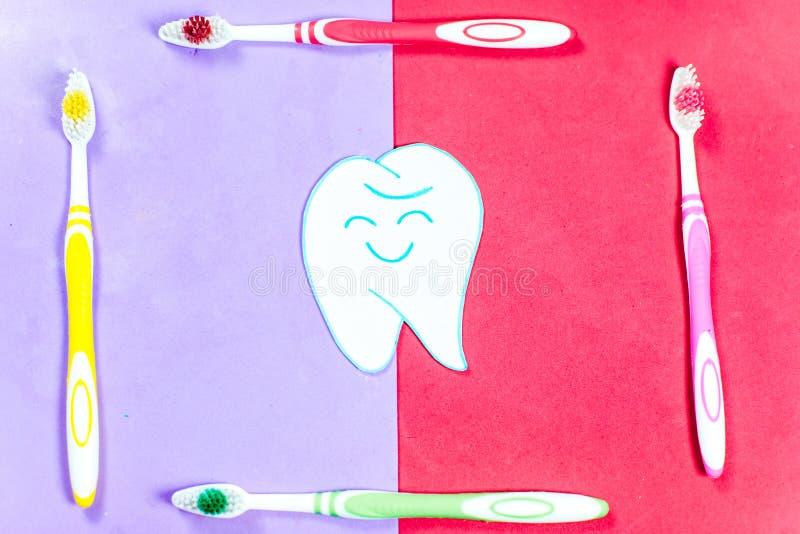 Escovas de dentes e um dentífrico em um fundo colorido fotografia de stock royalty free
