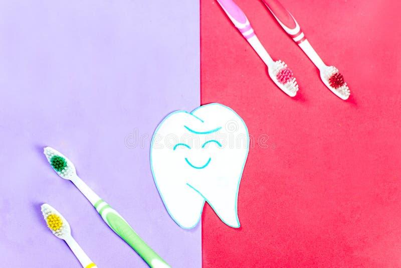 Escovas de dentes e um dentífrico em um fundo colorido imagem de stock royalty free