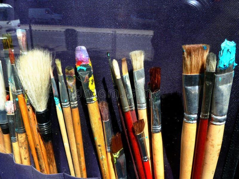 Escovas de pintura coloridas na janela de exposição da loja da fonte da arte imagens de stock