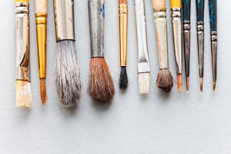 Escovas de pintura diferentes usadas do tamanho textura de madeira do pincel do estilo retro vista superior, foco macio, foto do  imagens de stock