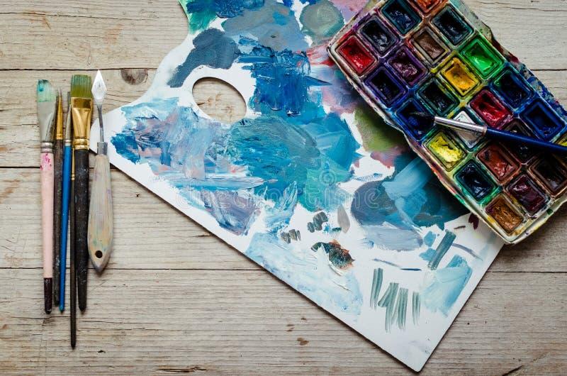 Escovas de pintura do artista e paintbox da aquarela fotografia de stock