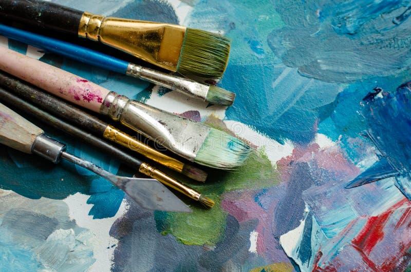 Escovas de pintura do artista na paleta de madeira fotos de stock royalty free