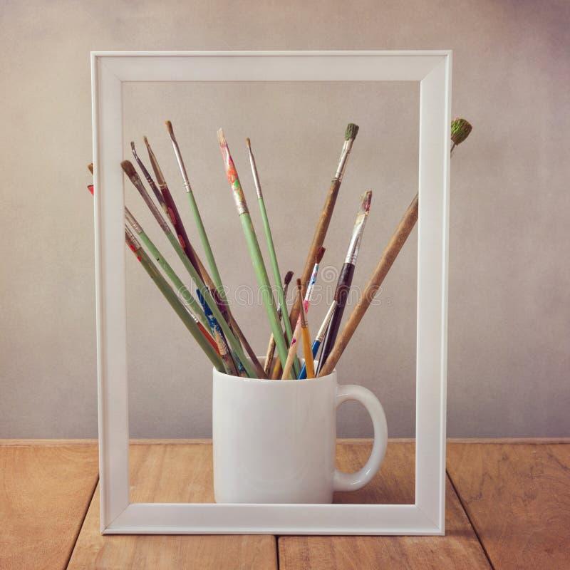 Escovas de pintura do artista na tabela de madeira com moldura para retrato imagens de stock royalty free