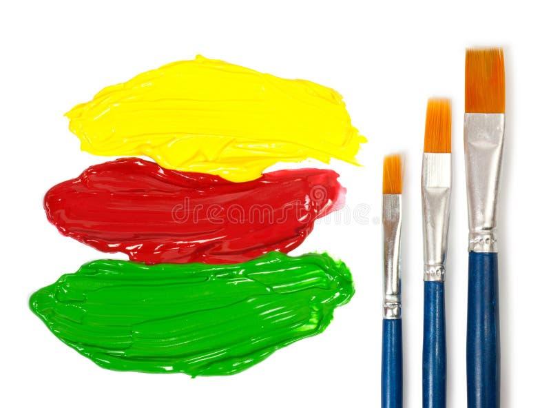 Escovas de pintura dos artistas e cor três da pintura fotos de stock royalty free
