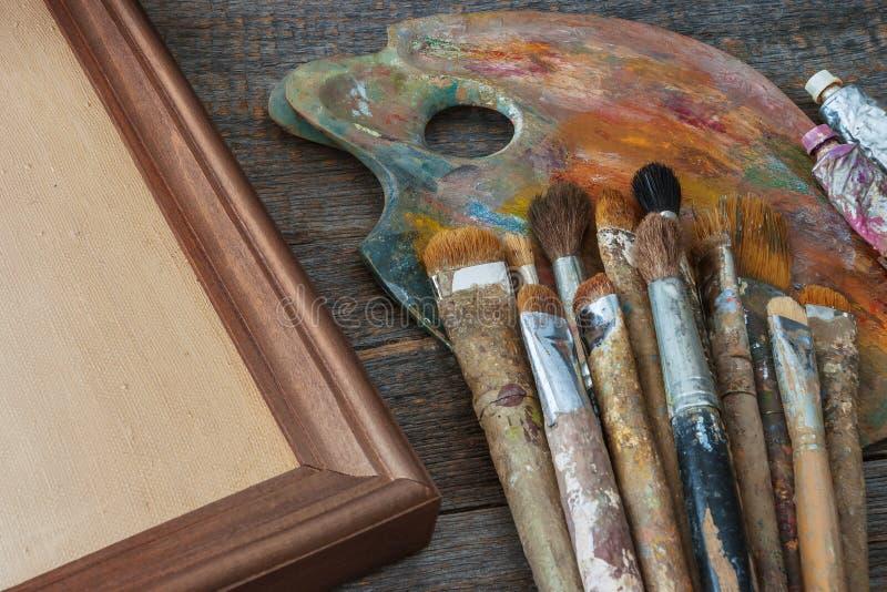 Escovas do artista, da pintura e da lona no quadro imagem de stock royalty free