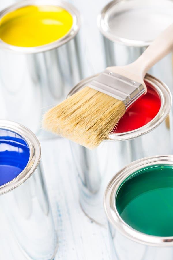 Escovas do close-up que encontram-se em latas coloridos da pintura fotografia de stock