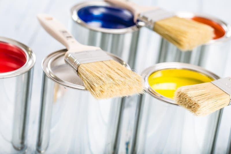 Escovas do close-up que encontram-se em latas coloridos da pintura foto de stock royalty free
