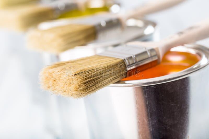 Escovas do close-up que encontram-se em latas coloridos da pintura imagens de stock