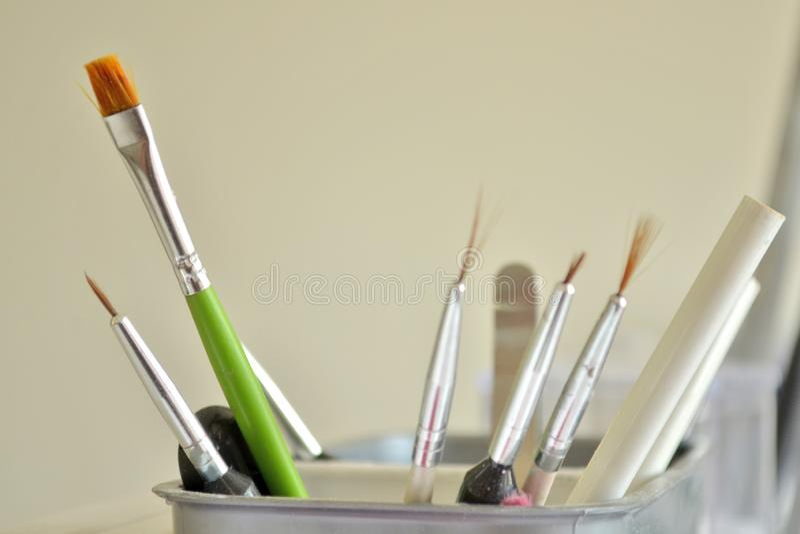 Escovas e ferramentas para a arte do tratamento de mãos e do prego em um vidro branco no salão de beleza no fundo de uma parede imagem de stock