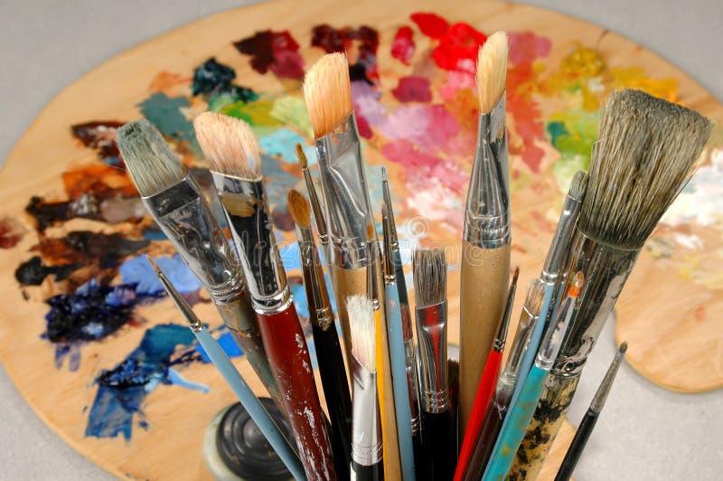 Escovas e paleta do artista fotos de stock