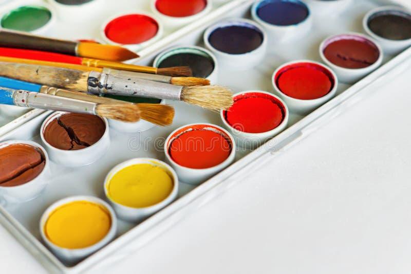 Escovas e pinturas do ` s do artista no fundo branco foto de stock