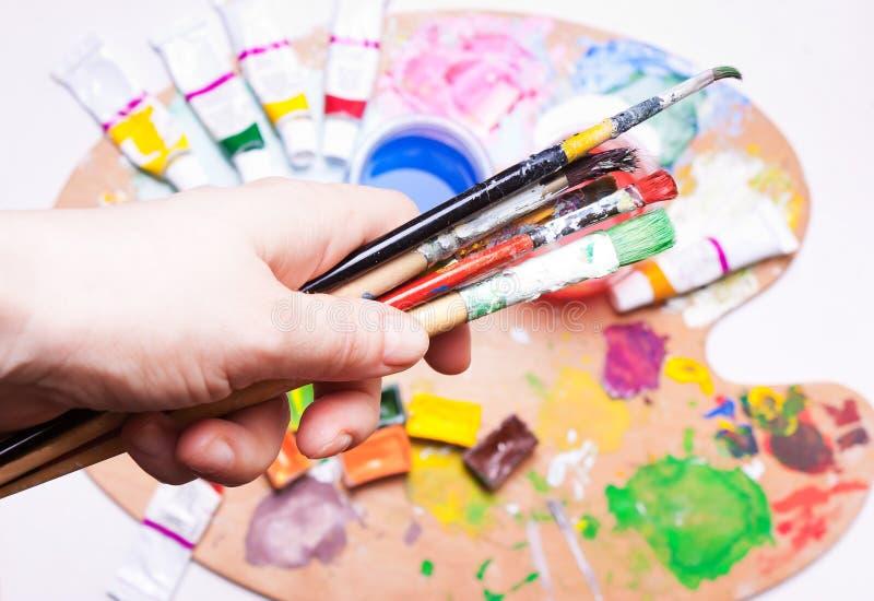 Escovas fêmeas das posses da mão sobre pinturas coloridas fotografia de stock royalty free