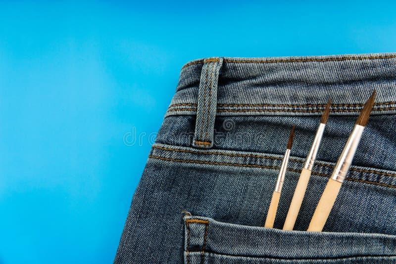 Escovas no bolso traseiro de women' azul; calças de brim de s fotos de stock