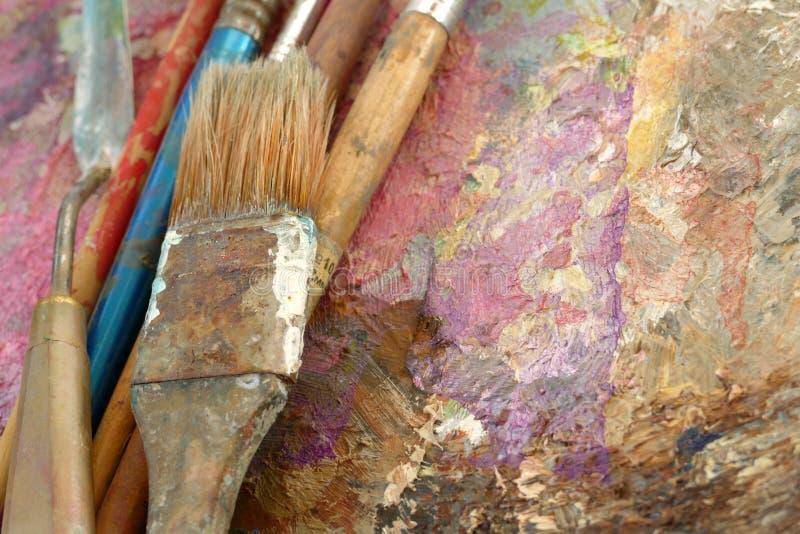 Escovas velhas da arte em uma paleta com pinturas Vista superior fotografia de stock royalty free