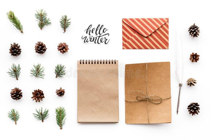 Escreva cumprimentos Envelope, papel, ramos spruce e cones e olá! rotulação da mão do inverno na opinião superior do fundo branco imagens de stock