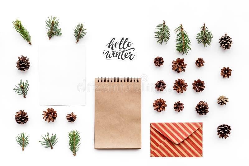 Escreva cumprimentos Envelope, papel, ramos spruce e cones e olá! rotulação da mão do inverno na opinião superior do fundo branco imagem de stock