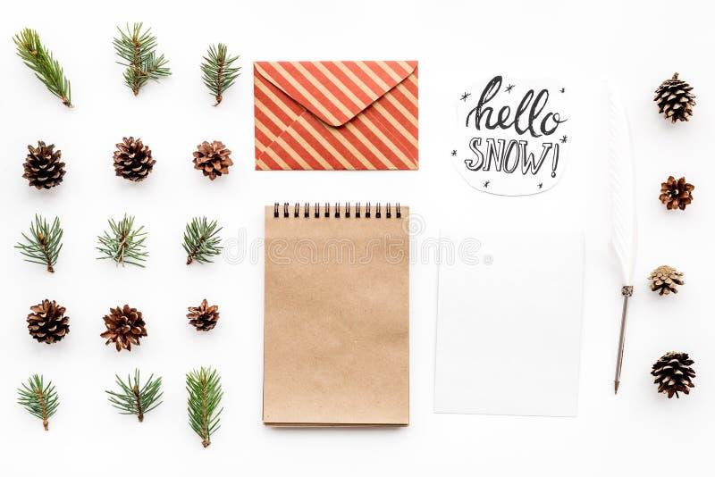 Escreva cumprimentos Envelope, papel, ramos spruce e cones e olá! rotulação da mão da neve na opinião superior do fundo branco imagens de stock