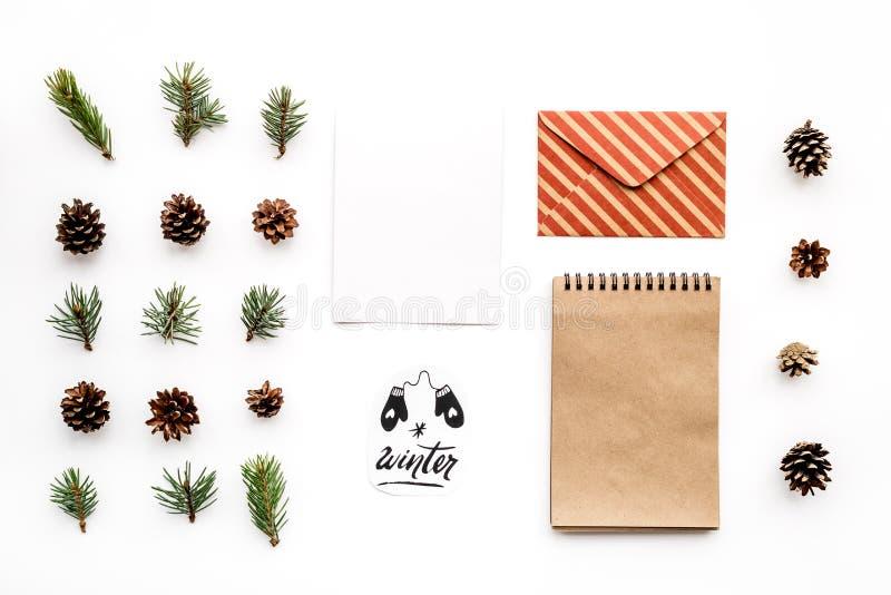 Escreva cumprimentos O envelope, o papel, os ramos e os cones spruce e o inverno entregam a rotulação na opinião superior do fund fotografia de stock royalty free