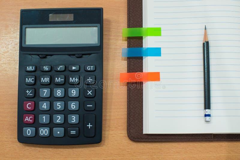 Escreva, a nota, a calculadora e o livro de papel na tabela de madeira Vista superior fotografia de stock royalty free