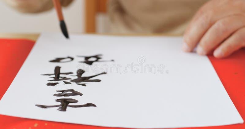 Escrevendo a caligrafia chinesa com significado da frase deseje-lhe boas FO imagens de stock