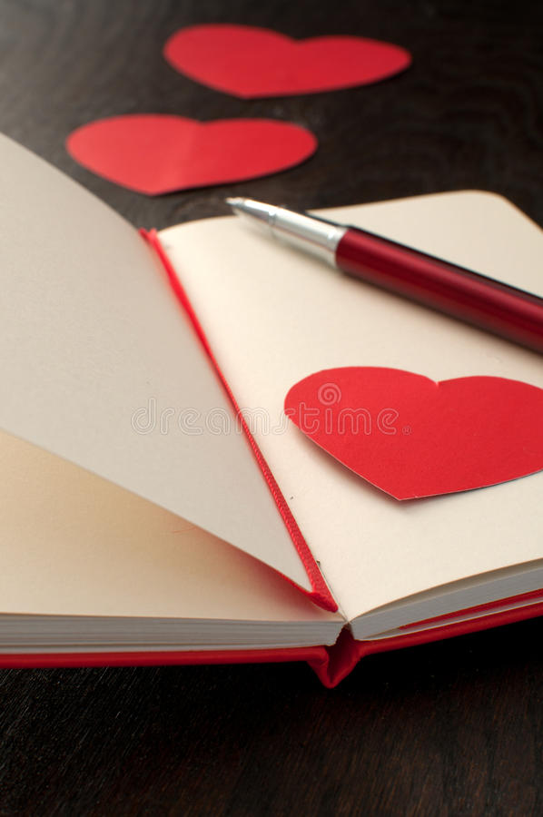 Escrevendo o poema ou o texto romântico no caderno fotografia de stock