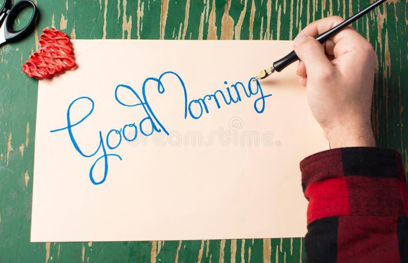 Escrevendo a uma nota do bom dia a vista superior imagens de stock