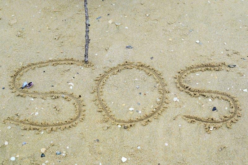 Escriba un símbolo para la ayuda en la arena foto de archivo