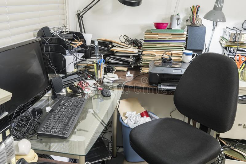 Escritório com a mesa desarrumado completa dos arquivos e da desordem imagens de stock