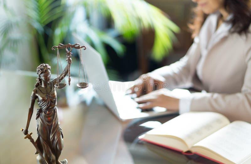 Escritório de advogado Estátua de justiça com escalas e do advogado que trabalha em um portátil imagem de stock royalty free