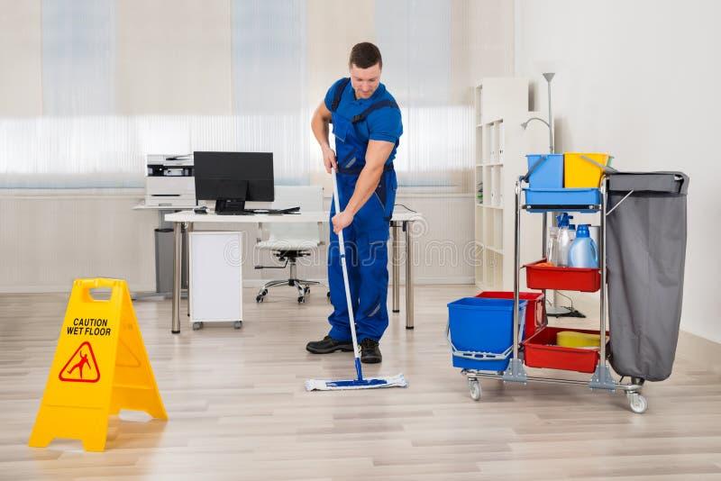 Escritório de Mopping Floor In do guarda de serviço foto de stock