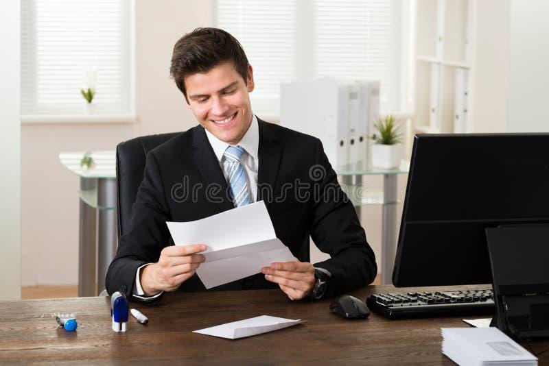 Escritório de Reading Paper In do homem de negócios imagem de stock