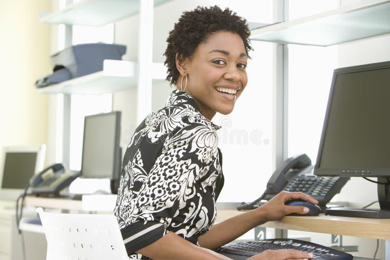 Escritório de sorriso de Using Computer In da mulher de negócios imagens de stock