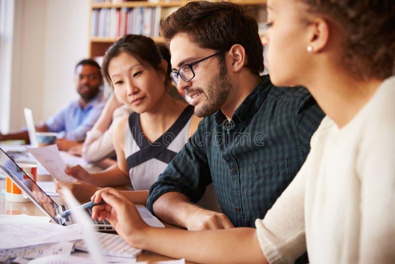 Escritório de Team Having Meeting In Busy do negócio imagens de stock