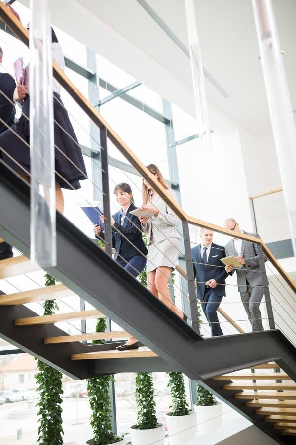 Escritório de Team Moving Upstairs In Modern do negócio imagem de stock