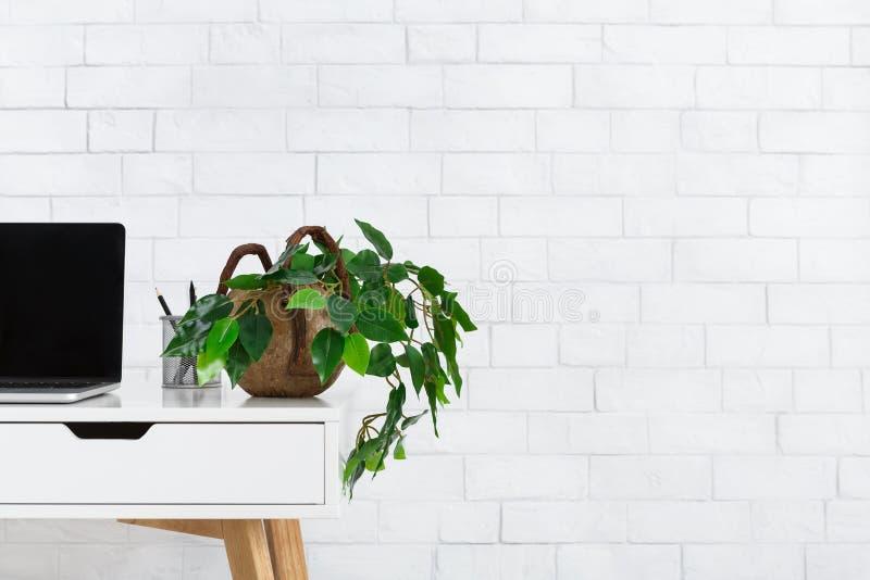 Escritório domiciliário de Minimalistic Local de trabalho com houseplant e portátil fotografia de stock