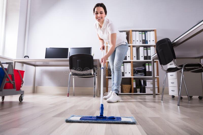 Escritório fêmea de Cleaning Floor In do guarda de serviço imagens de stock