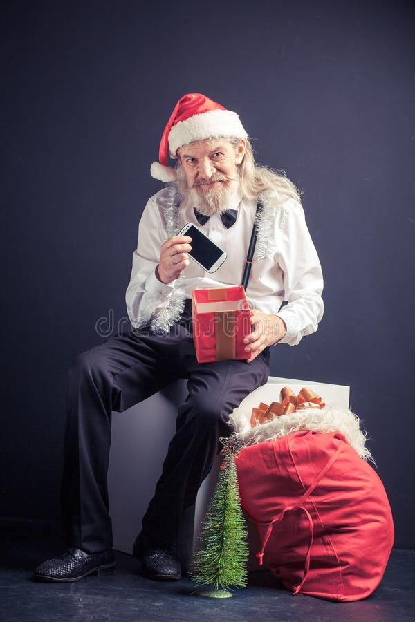 Escritório feliz Santa que guarda o telefone celular como o presente do Natal foto de stock royalty free