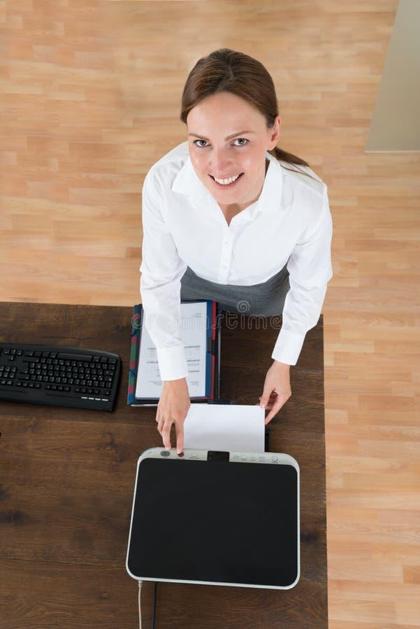 Escritório novo de Using Printer In da mulher de negócios foto de stock