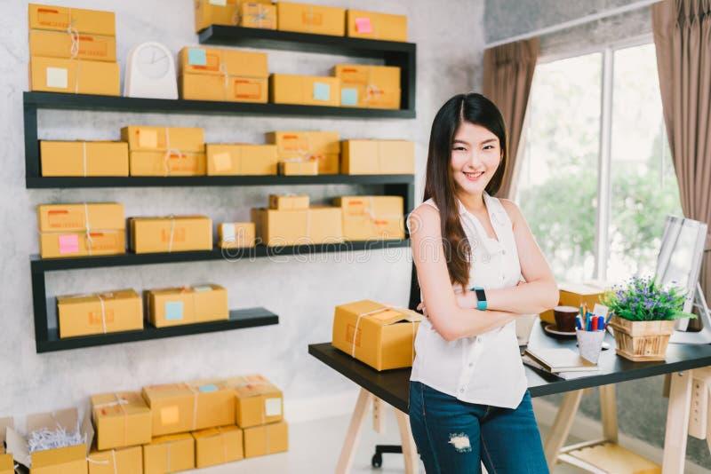 Escritório pequeno asiático novo do proprietário empresarial em casa, empacotamento em linha do mercado e cena da entrega imagens de stock