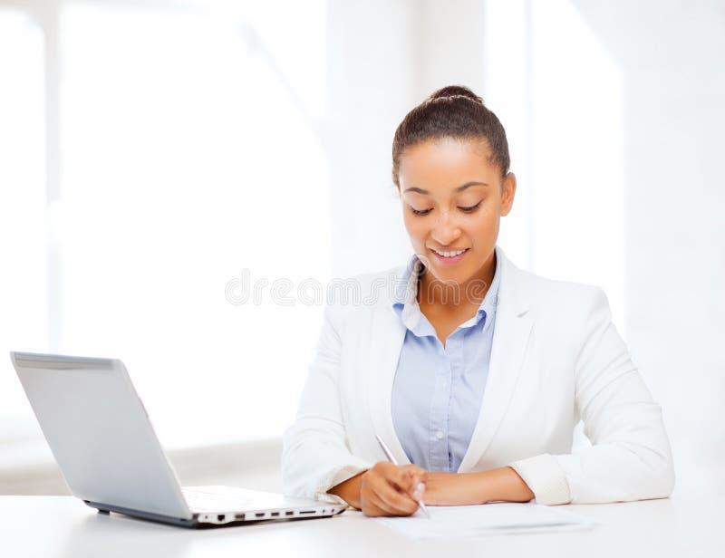 Escrita africana da mulher de negócios algo fotografia de stock royalty free