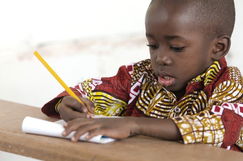 Escrita africana pequena adorável da criança na escola em Bamako, Mali imagens de stock