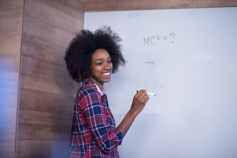 Escrita afro-americano da mulher em um quadro em um offic moderno imagem de stock royalty free