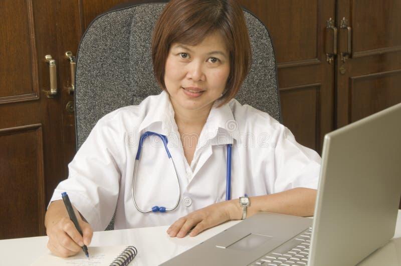 Escrita amigável do doutor em sua mesa imagens de stock royalty free