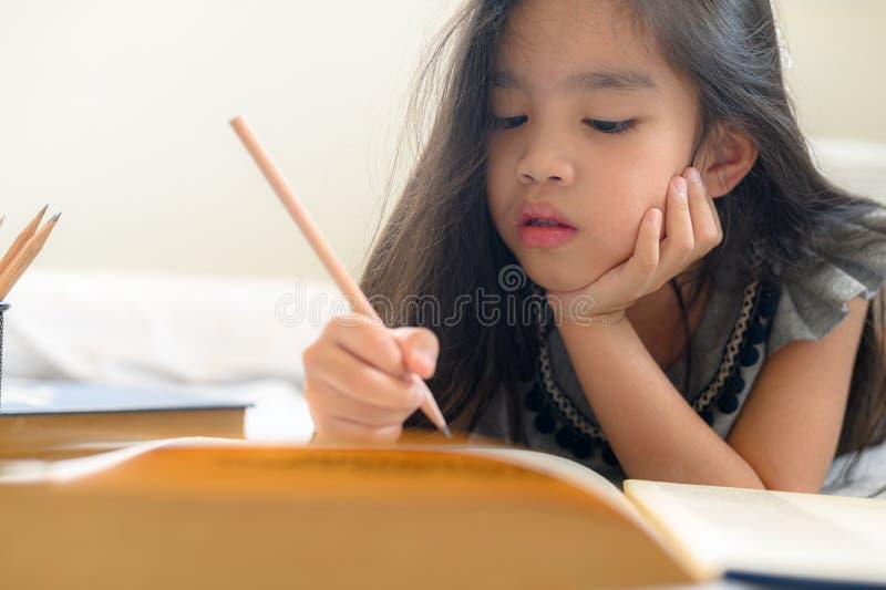 Escrita asiática da menina com lápis e caderno foto de stock