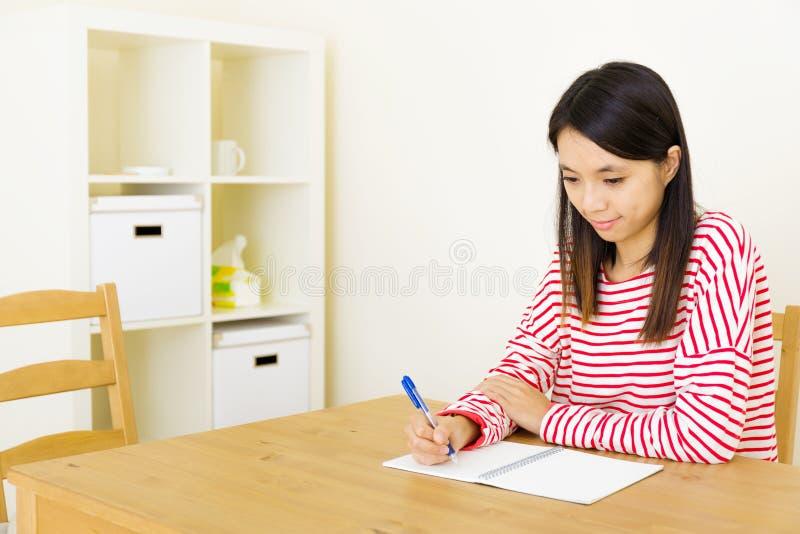 Escrita asiática da mulher no caderno fotos de stock