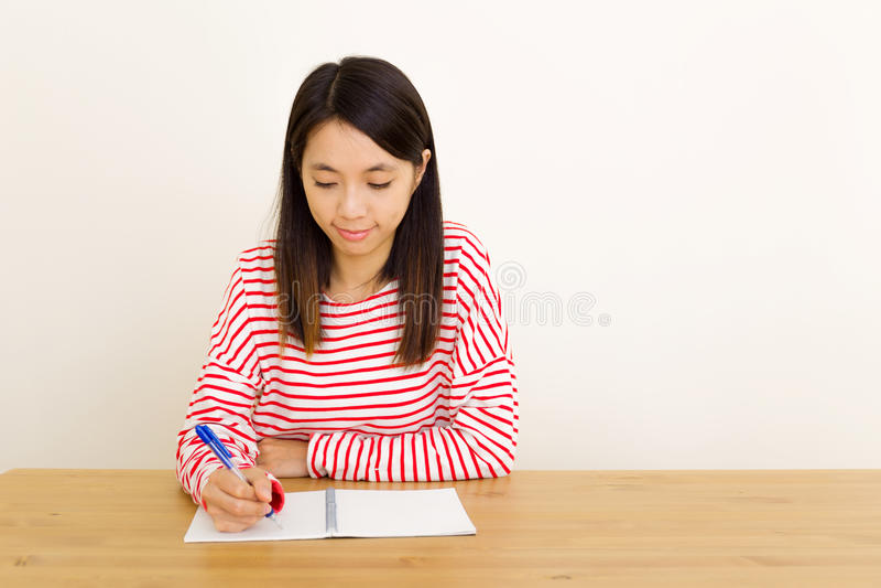 Escrita asiática da mulher no caderno fotografia de stock royalty free