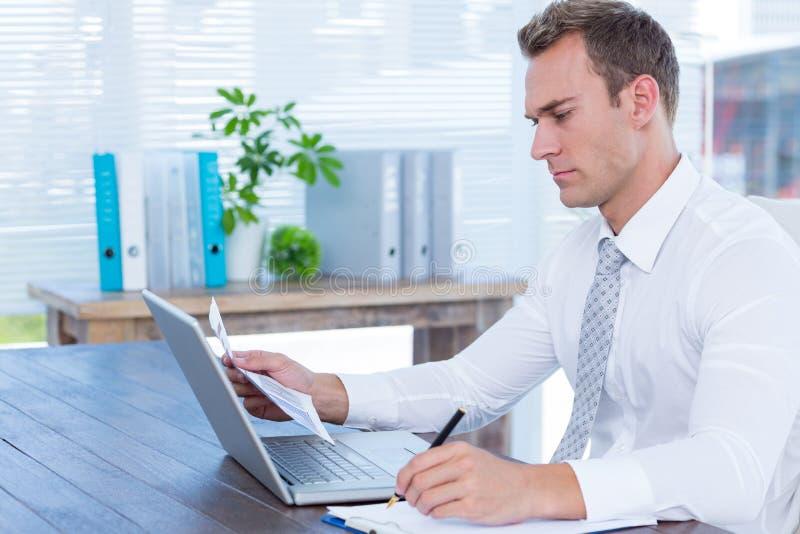Escrita atenta do homem de negócios no caderno fotografia de stock royalty free
