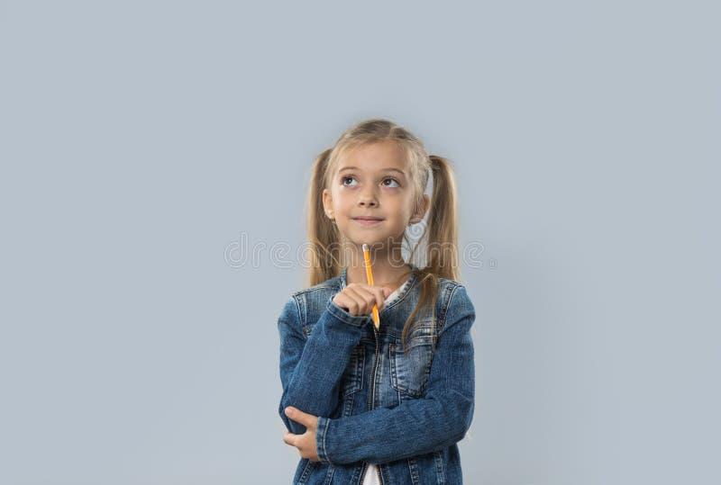 Escrita bonita do lápis da posse da menina que pensa a vista de sorriso feliz para copiar o espaço isolado imagens de stock